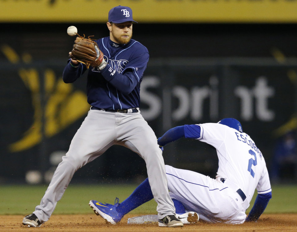 Photo - Tampa Bay Rays second baseman Ben Zobrist bobbles the ball as Kansas City Royals' Alcides Escobar (2) slides into second base during the third inning of a baseball game at Kauffman Stadium in Kansas City, Mo., Tuesday, April 8, 2014. Escobar was called safe and review of the play stood. (AP Photo/Orlin Wagner)