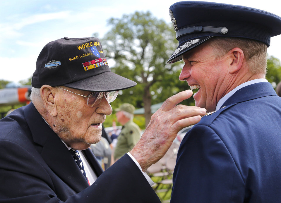 Photo - World War II veteran Donald Wright, 96, left, reaches to touch the star on the shoulder of keynote speaker Brig. Gen. David Burgy, Chief of Staff, Joint Force Headquarters, Oklahoma Air National Guard, after the 45th Infantry Division Museum's Memorial Day Ceremony on Monday, May 30, 2016. Burgy laughs when Wright, who has diminished vision, put his hand on the uniform epaulette  to feel the star after he asked Burgy what his rank is as the two men visited after the ceremony. Wright was one of five brothers serving in the war during the 1940s. He was in the US Army and fought in the Pacific Theater in the battle at Guadalcanal. He had an older brother who was killed by enemy fire 11 days after Wright arrived on the island. Wright also had another brother who served with him at Guadalcanal. He retired from the Army with the rank of major.  Photo by Jim Beckel, The Oklahoman