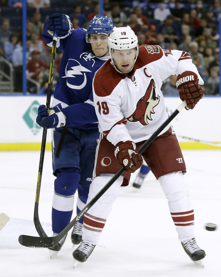 Photo - Phoenix Coyotes right wing Shane Doan (19) looks to deflect the puck as he stands in front of Tampa Bay Lightning defenseman Matt Carle (25) during the first period of an NHL hockey game, Monday, March 10, 2014, in Tampa, Fla. (AP Photo/Chris O'Meara)