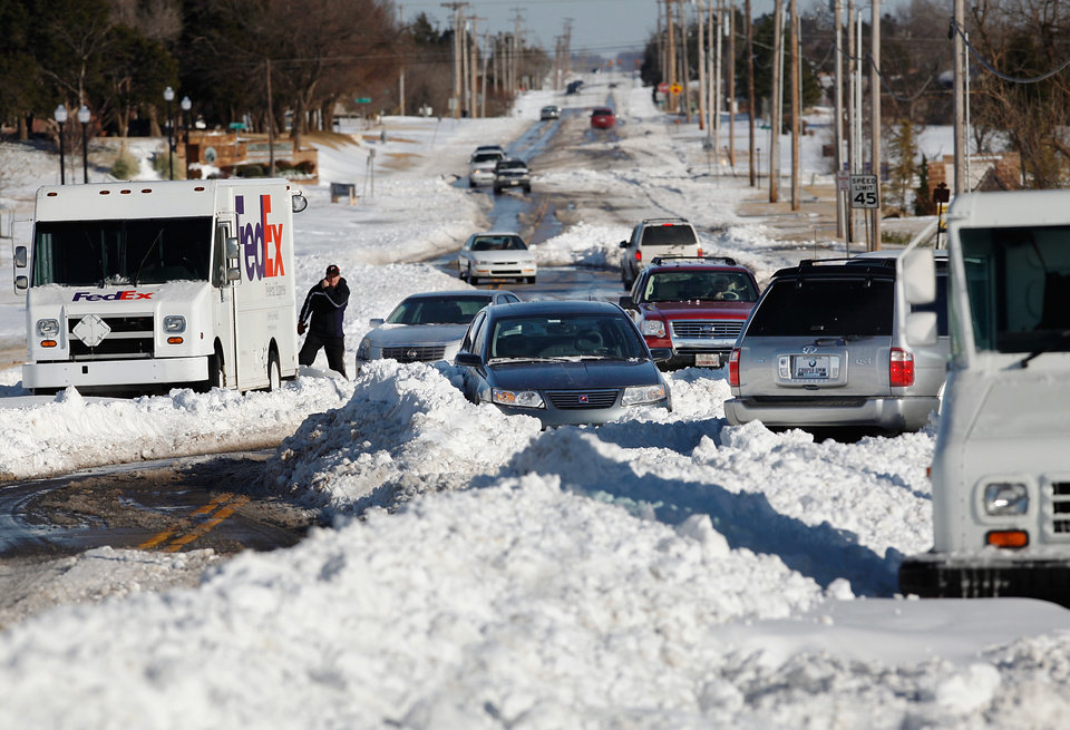 Traffic on Britton Road between Broadway and Kelley maneuvers around at least four stuck vehicles as owners returned to dig them out. Many spent Christmas Day, Dec. 25, 2009,  digging out from record snow storm that dumped 14 inches of snow in the Oklahoma City area.   Photo by Jim Beckel, The Oklahoman