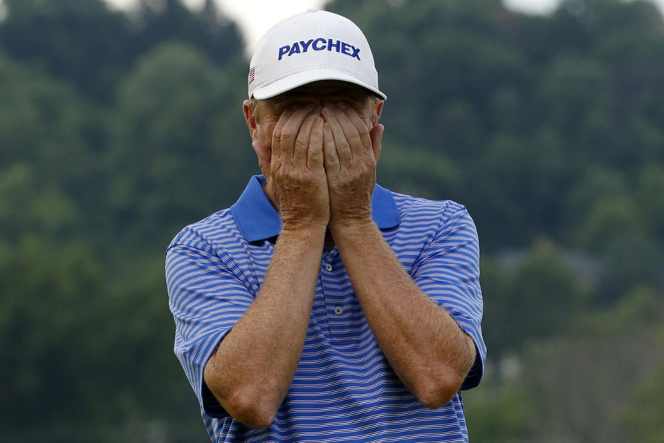 Photo - Jeff Sluman reacts to missing a birdie putt on the first hole of a playoff with Bernhard Langer of Munich, Germany, during the final round of the Senior Players Championship golf tournament at Fox Chapel Golf Club in Pittsburgh, Sunday, June 29, 2014. Langer sunk a birdie putt on the second hole of the playoff to win the Senior Players Championship. (AP Photo/Gene J. Puskar)
