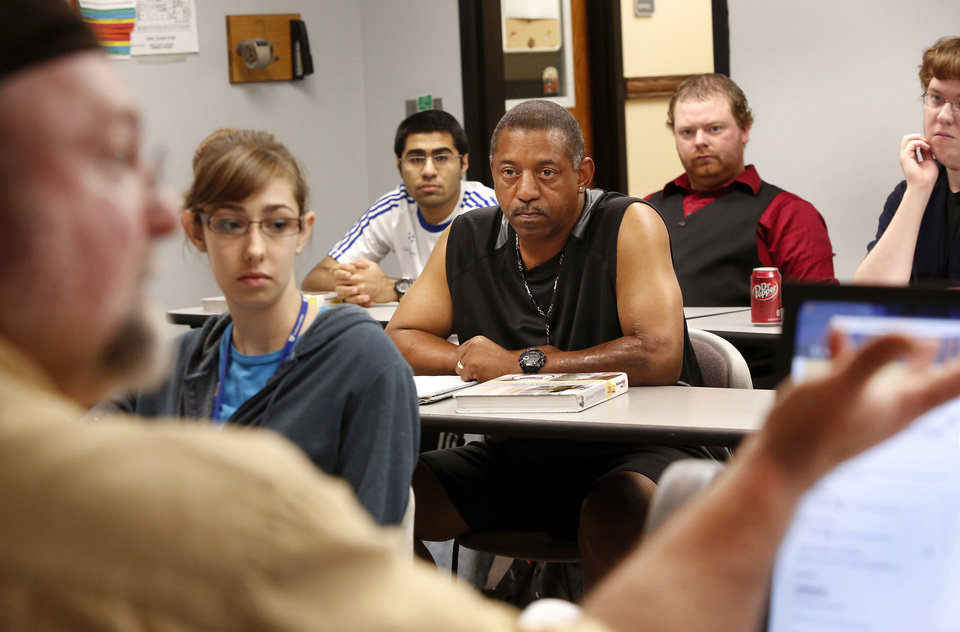 Photo - Craig Dawkins teaches a personal finance class at Rose State College in Midwest City  that includes a few adult college students. Anthony Scott sits among younger students in the class on Thursday. Photo  by Jim Beckel, The Oklahoman.  Jim Beckel - THE OKLAHOMAN