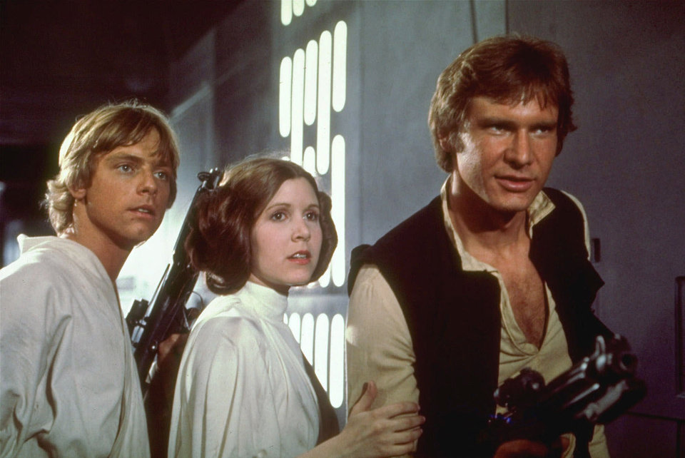 Photo - FILE--Mark Hamill, left, Carrie Fisher, center, and Harrison Ford, right, are shown in a scene from the 1977 film