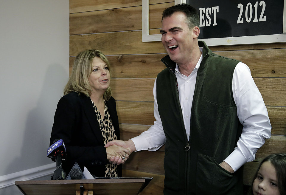 Photo - Oklahoma Gov. Kevin Stitt laughs with  Rhonda Bear shortly before signing her pardon at She Brews Coffee House in Claremore Thursday, Nov. 7, 2019. MIKE SIMONS/Tulsa World
