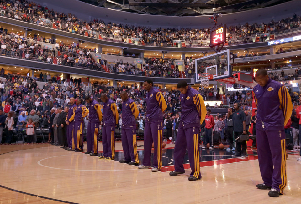 Photo - Under dimmed lights, the Los Angeles Lakers and the Washington Wizards observe a moment of silence to honor the victims of the school shootings in Connecticut, before an NBA basketball game Friday, Dec. 14, 2012 in Washington. (AP Photo/Alex Brandon)
