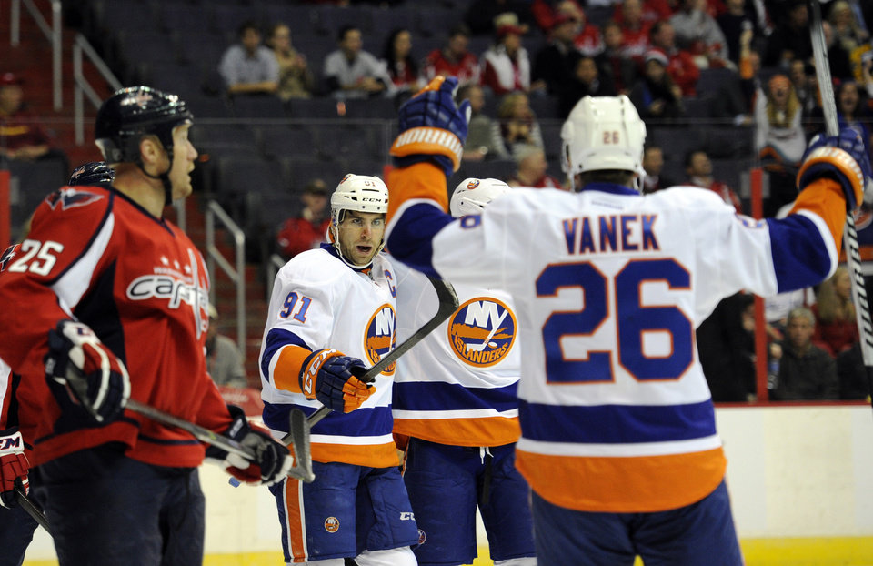 Photo - New York Islanders center John Tavares (91) celebrates his goal with teammate Thomas Vanek (26), of Austria, and others as Washington Capitals left wing Jason Chimera (25) skates by during the first period an NHL hockey game, Tuesday, Nov. 5, 2013, in Washington. (AP Photo/Nick Wass)