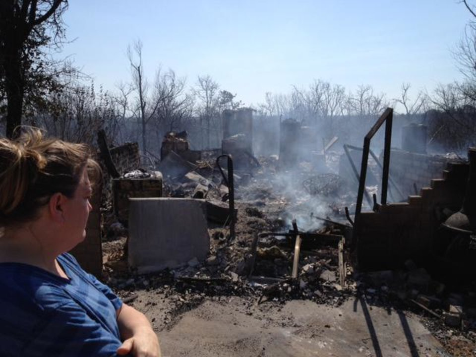 Photo - Residents survey the aftermath of wildfires that spread through Luther and Cleveland County on Friday. About 25 homes and a day care center were destroyed by the fire in Luther. In Cleveland County, several homes were destroyed by the fire near Norman, Slaughterville and Noble. Photo by James Beckel, The Oklahoman