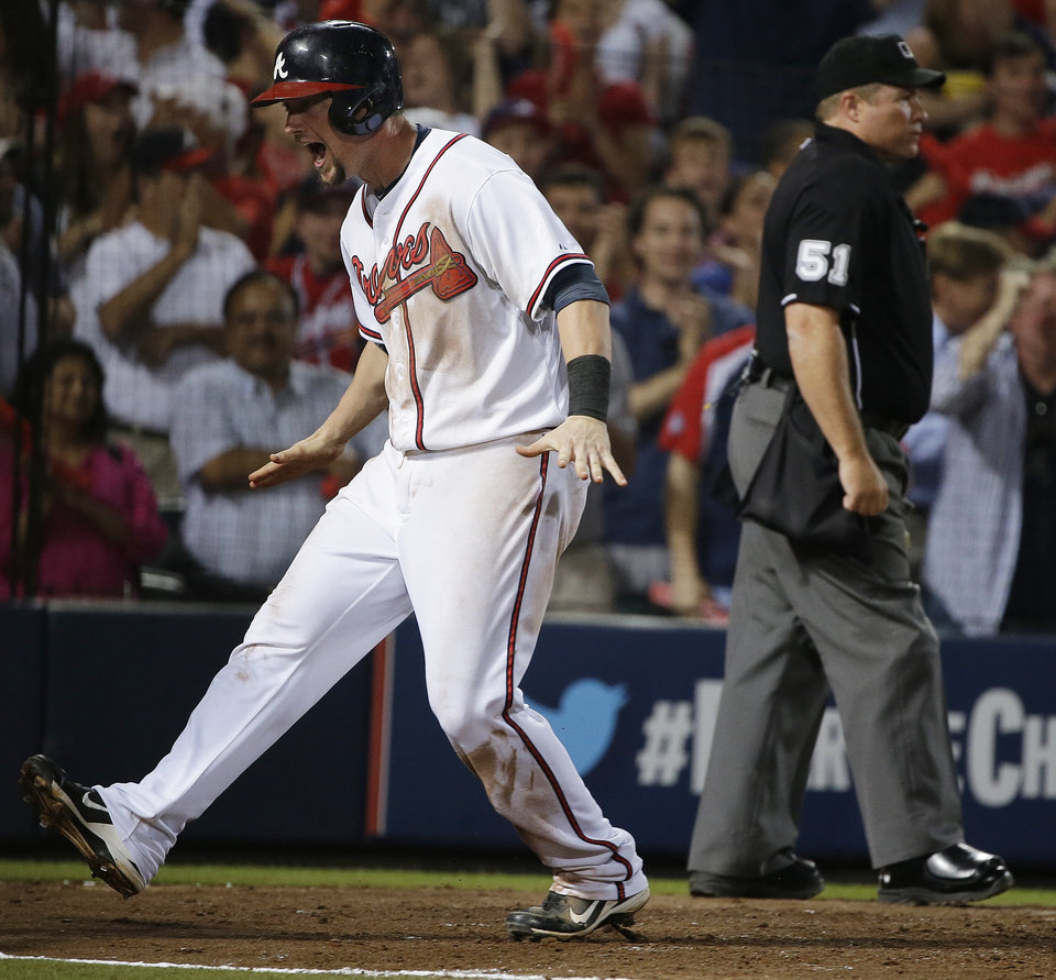 Photo - Atlanta Braves' Chris Johnson, left, celebrates after scoring on teammate Jason Heyward's single in the seventh inning of Game 2 of the National League division series against the Los Angeles Dodgers, Friday, Oct. 4, 2013, in Atlanta. (AP Photo/John Bazemore)