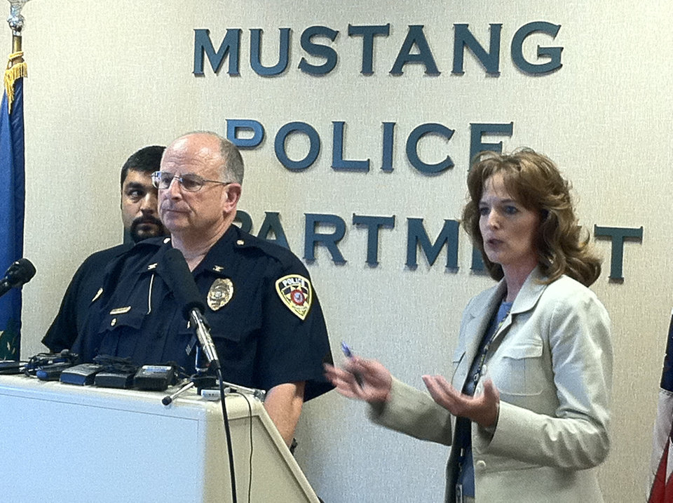 Photo - The Mustang police chief and OSBI spokeswoman Jessica Brown address the media today. Photo by Chris Landsberger