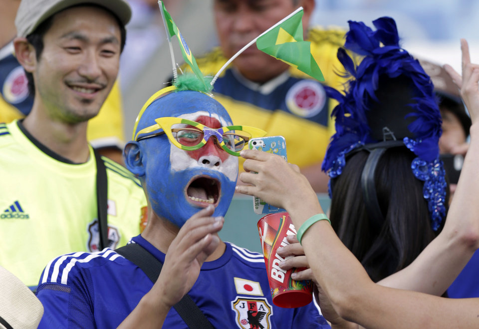 Photo - A fan with the colors of the Japanese flag painted on his face reacts as he looks at a smartphone photo before the group C World Cup soccer match between Japan and Colombia at the Arena Pantanal in Cuiaba, Brazil, Tuesday, June 24, 2014. (AP Photo/Dolores Ochoa)