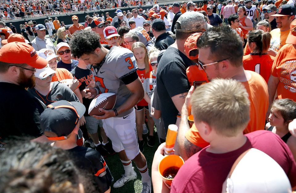 Photo - Oklahoma State's Spencer Sanders (3) signs autographs for fans following during the Oklahoma State Cowboys spring practice at Boone Pickens Stadium in Stillwater, Okla., Saturday, April 20, 2019.  Photo by Sarah Phipps, The Oklahoman
