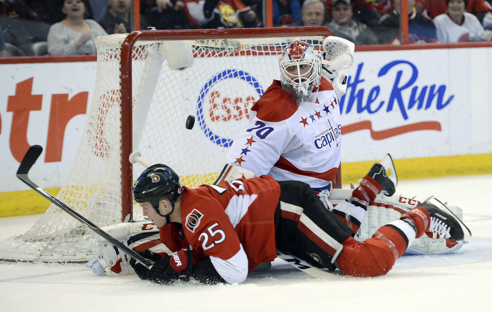 Photo - Washington Capitals goalie Braden Holtby (70) makes a save on Ottawa Senators Chris Neil (25) during the second period of an NHL game in Ottawa, Ontario on Thursday, April 18, 2013. (AP Photo/The Canadian Press, Justin Tang)