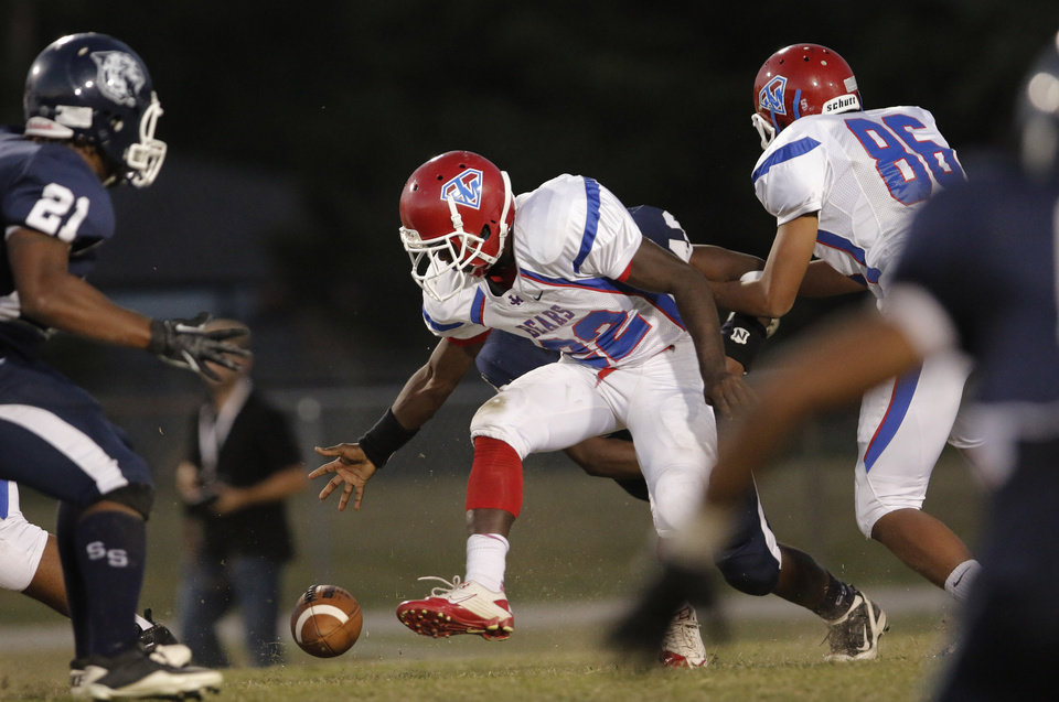 JM #22 Lequan Swain drops the ball, but picked it back up and stayed in stride for a gain during the high school football game of John Marshall at Star Spencer, Thursday, September 26, 2013. Photo by Doug Hoke, The Oklahoman