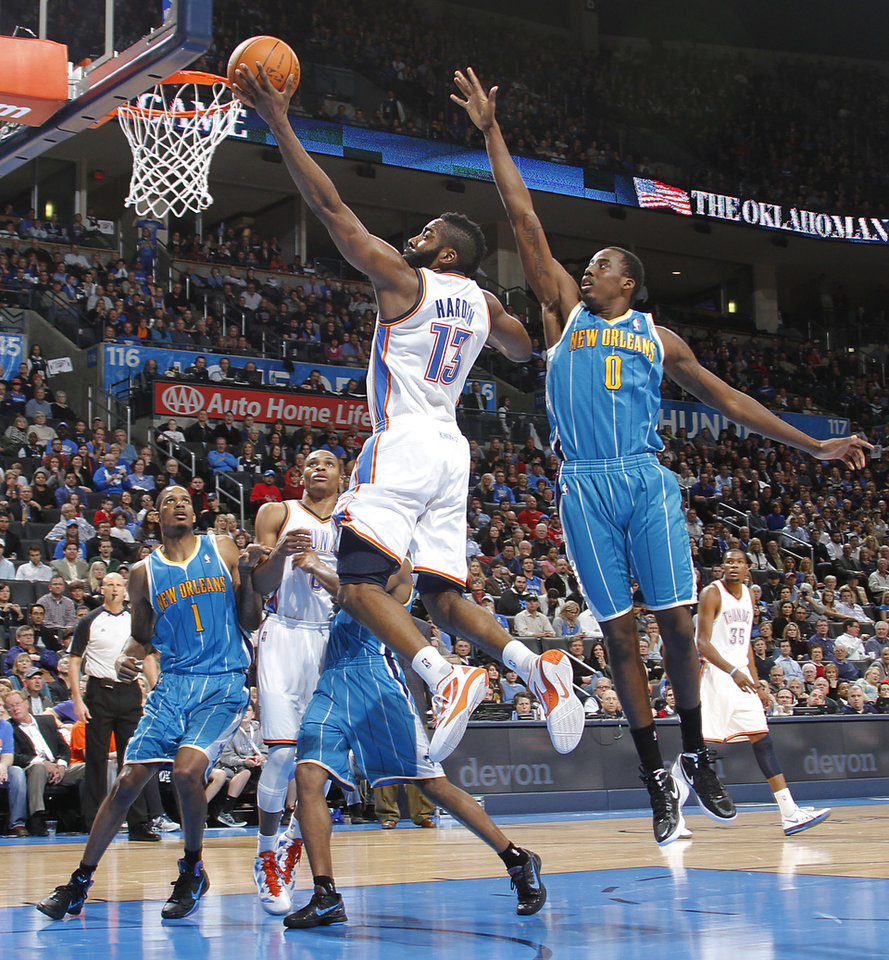 Photo - Oklahoma City Thunder guard James Harden (13) drives to the basket past New Orleans Hornets small forward Al-Farouq Aminu (0) during the NBA basketball game between the Oklahoma City Thunder and the New Orleans Hornets at the Chesapeake Energy Arena on Wednesday, Jan. 25, 2012, in Oklahoma City, Okla. Photo by Chris Landsberger, The Oklahoman
