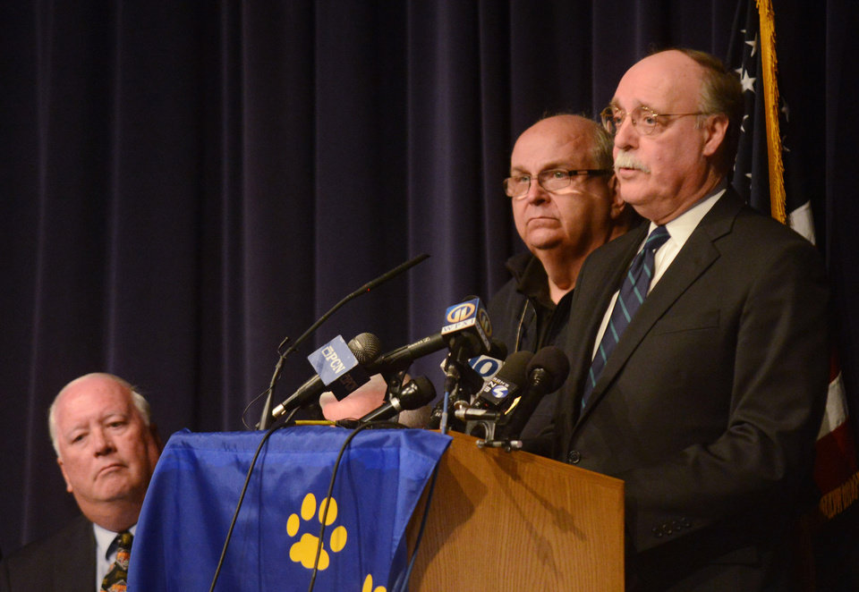 Photo - Westmoreland County DA John W. Peck, right, takes questions  during a press conference while Murrysville Mayor Robert J. Brooks, left, and Westmoreland County Public Safety PIO Dan Stevens look on at Franklin Regional Middle School on Wednesday, April 9, 2014.  Governor Tom Corbett paid a visit to Franklin Regional to address the stabbing incident occurring earlier in the day at Franklin Regional High School.  (AP Photo/Tribune Review, Evan Sanders)  PITTSBURGH OUT