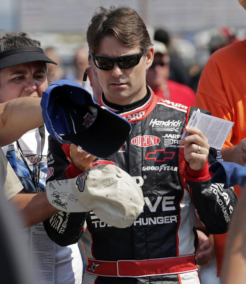 NASCAR driver Jeff Gordon fights his way through a sea of hats held by autograph seekers as he walks to pit road at Talladega Superspeedway in Talladega, Ala., Saturday, Oct. 6, 2012. The drivers were qualifying for the Sunday running of the NASCAR Sprint Cup Series auto race. (AP Photo/Dave Martin)