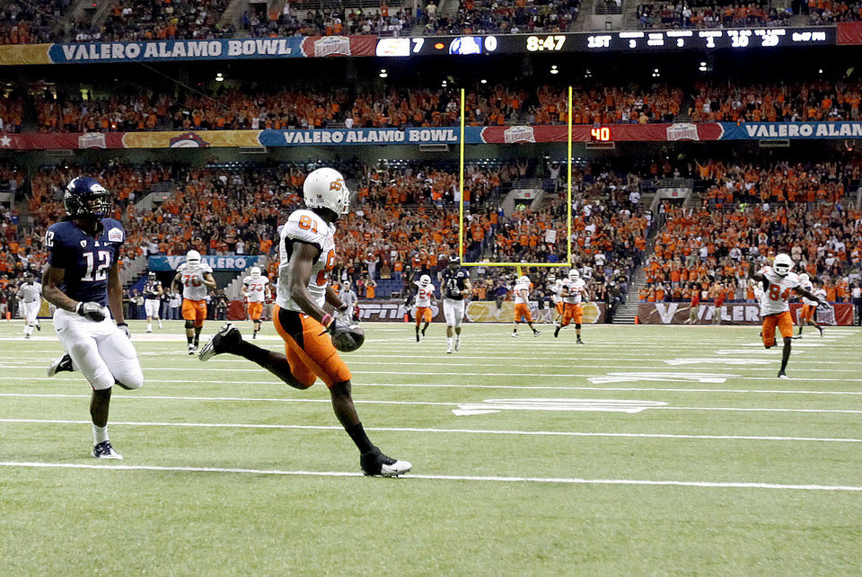 Photo - Oklahoma State's Justin Blackmon (81) tip-toes the goal line before scoring a touchdown in front of Arizona's Adam Hall (12) during the Valero Alamo Bowl college football game between the Oklahoma State University Cowboys (OSU) and the University of Arizona Wildcats at the Alamodome in San Antonio, Texas, Wednesday, December 29, 2010. Photo by Sarah Phipps, The Oklahoman