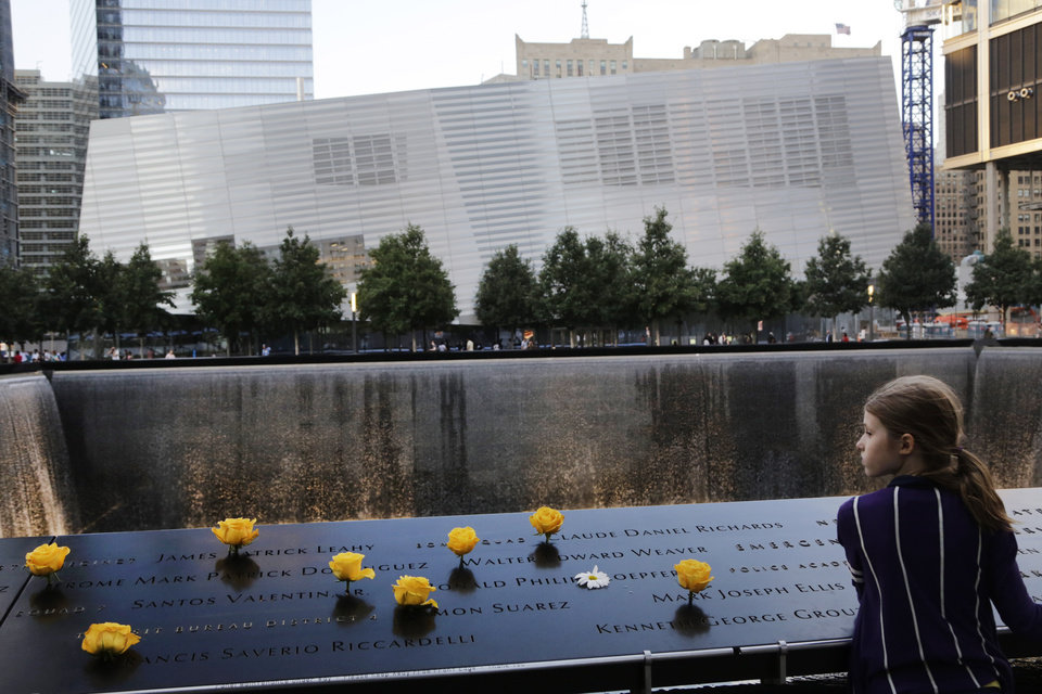 Photo - Charlotte Newman, 8, visits the National September 11 Memorial and Museum, Sunday, Sept. 8, 2013, in New York. Twelve years after terrorists destroyed the old World Trade Center, the new World Trade Center is becoming a reality, with a museum commemorating the attacks and two office towers where thousands of people will work set to open within the next year. (AP Photo/Mark Lennihan)