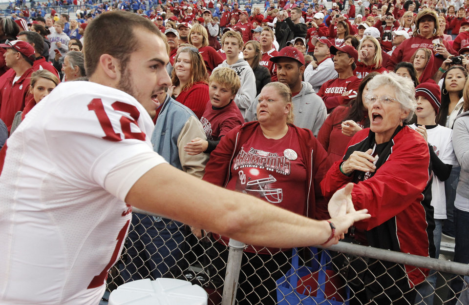 Photo - OU quarterback Landry Jones (12) celebrates with fans after the college football game between the University of Oklahoma Sooners (OU) and the University of Kansas Jayhawks (KU) on Saturday, Oct. 24, 2009, in Lawrence, Kan. OU won, 35-13. Photo by Nate Billings, The Oklahoman