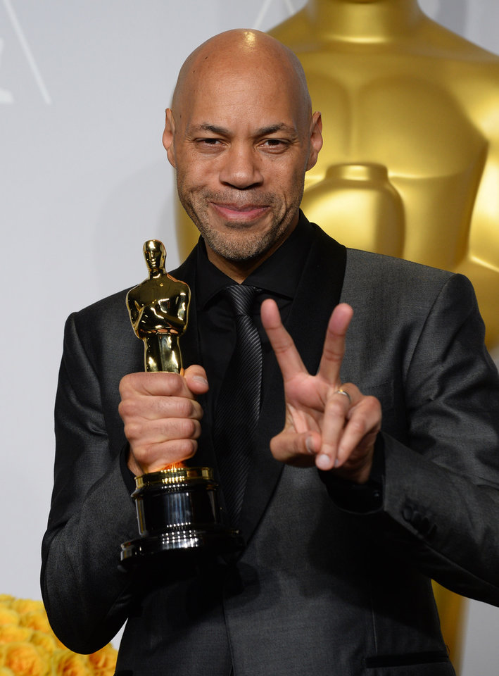 Photo - John Ridley poses in the press room with the award for best adapted screenplay of the year for