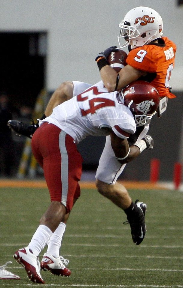 Photo - OSU's Bo Bowling (9) makes a catch as he is tackled by WSU's Daniel Simmons (24) during the college football game between the Washington State Cougars (WSU) and the Oklahoma State Cowboys (OSU) at Boone Pickens Stadium in Stillwater, Okla., Saturday, September 4, 2010. Photo by Sarah Phipps, The Oklahoman