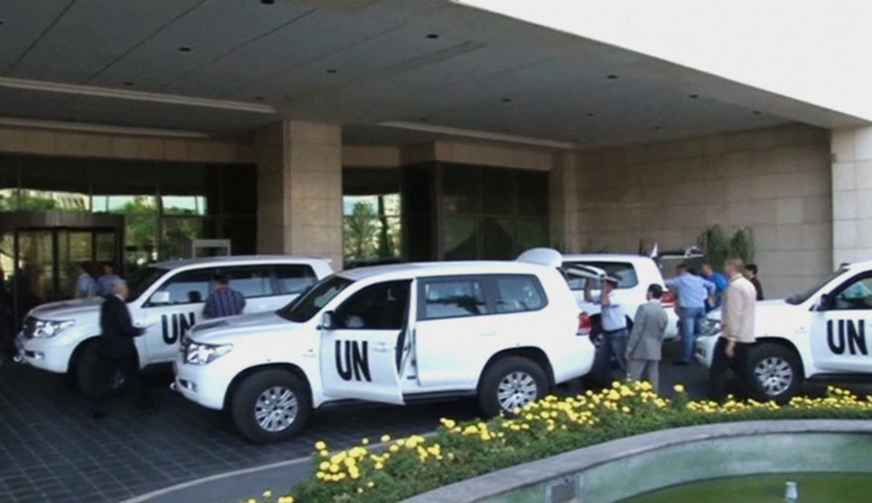 Photo - In this image made from video, U.N. weapon inspectors gets off their vehicles as they arrive at a hotel in Damascus, Syria, Sunday, Aug. 18, 2013. A team of U.N. weapons inspectors arrived in Damascus on Sunday for a long-delayed mission to investigate the alleged use of chemical arms in Syria's civil war. (AP Photo/AP Video)