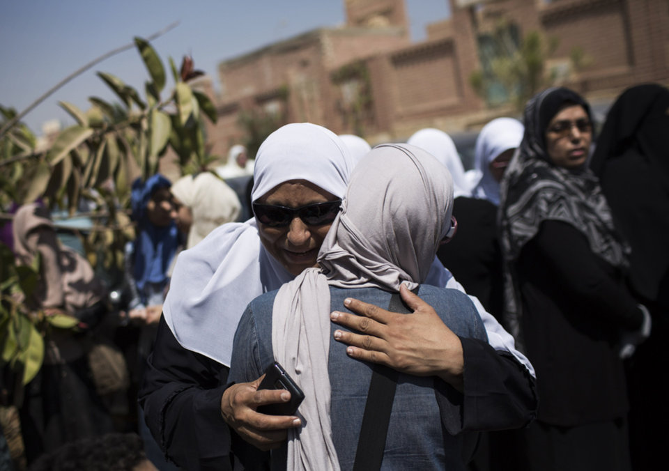 Photo - Relatives of Ammar Badie, the son of Muslim Brotherhood's spiritual leader Mohammed Badie, who was killed Friday by Egyptian security forces during clashes in Ramses Square, cry while attending his burial in Cairo's Katameya district, Egypt, Sunday, Aug. 18, 2013. Egyptian authorities raided homes of Muslim Brotherhood members Sunday in an apparent attempt to disrupt the group ahead of mass rallies by supporters of the country's ousted president. (AP Photo/Manu Brabo)