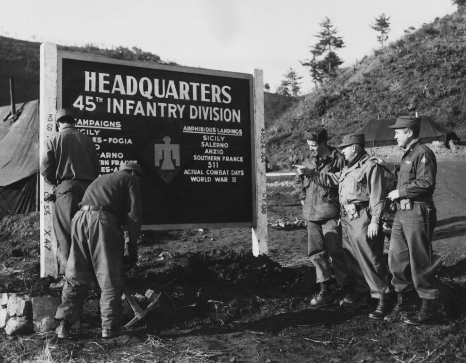 """Photo - With the 45th """"Thunderbird"""" division in Korea--The 45th Infantry division headquarters sign is now set up in its fifth location since it was painted after World War II--in a mountain niche near the Korean battlefront.  Listing the accomplishments of the World War II Thunderbird division, the sign has previously decorated the landscape at Lincoln Park armory, Oklahoma City; Fort Sill, Okla.; Camp Polk, La., and Camp Crawford, Hokkaido, Japan.  Two division old-timers tell the story of the sign to a newcomer, left above, Pfc. Gordon Mason jr., a member of the division's headquarter company from 394 E. Beecher Street, Milwaukee, Wisc.  The son of Mr. and Mrs. Gordon Mason Sr. , Emsdale, Ontario, he joined the division in January, 1951, at Camp Polk.  The old-timers are Lieut. Col. John McCasland, division provost marshal from Atoka, center, and Lieut. Col. George A. Fisher, military government officer, Oklahoma City, Okla.  McCasland joined the division in July, 1926, and Fisher in October, 1933.  U.S. army photo by Jack Gunter.  Original image undated.  Entered the library on 01/25/1952."""