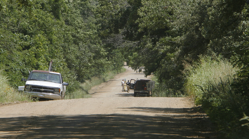 Photo - OSBI investigators closed the road past the crime scene to look for more clues in the deaths of Taylor Paschal-Placker and Skyla Whitaker who were shot and killed last Sunday on the dirt road near one of their homes, Thursday, June 12, 2008. The white truck is parked at the driveway of the Placker home and the man in the road is at the crime scene.   Photo by David McDaniel/The Oklahoman