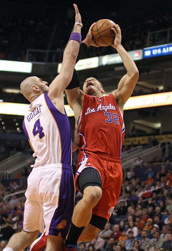 Los Angeles Clippers' Blake Griffin (32) drives to the basket past Phoenix Suns' Marcin Gortat of Poland during the first half of an NBA basketball game Sunday, Dec. 23, 2012, in Phoenix. (AP Photo/Ralph Freso)