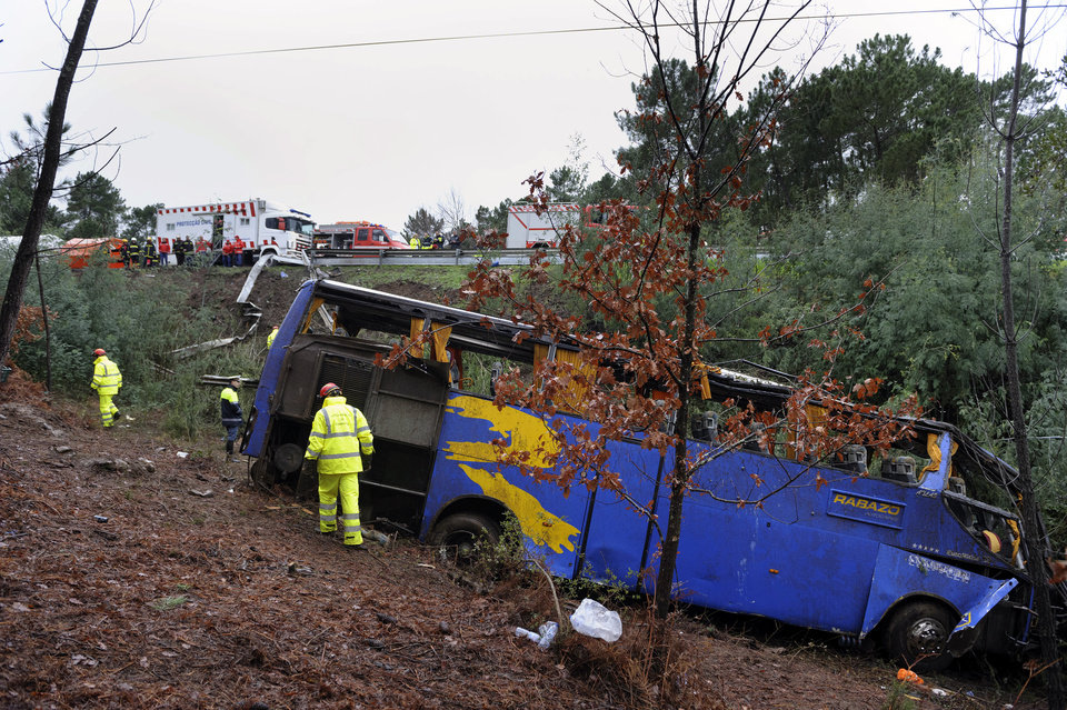 Photo - Portuguese firefighters work around the wreckage of a bus which ran off the road and crashed into a ravine, killing 10 people and injuring 33, officials said, in Serta, central Portugal, Sunday, Jan. 27, 2013. National Civil Protection authority spokesman Carlos Guerra says the injured have been taken to hospitals in the cities of Coimbra and Castelo Branco. (AP Photo/Sergio Azenha) PORTUGAL OUT