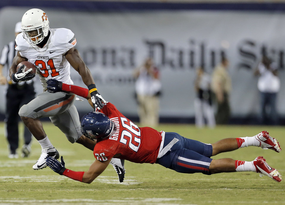 Photo - Oklahoma State's Jeremy Smith (31) gets by Arizona's Jourdon Grandon (26) during the college football game between the University  of Arizona and Oklahoma State University at Arizona Stadium in Tucson, Ariz.,  Sunday, Sept. 9, 2012. Photo by Sarah Phipps, The Oklahoman