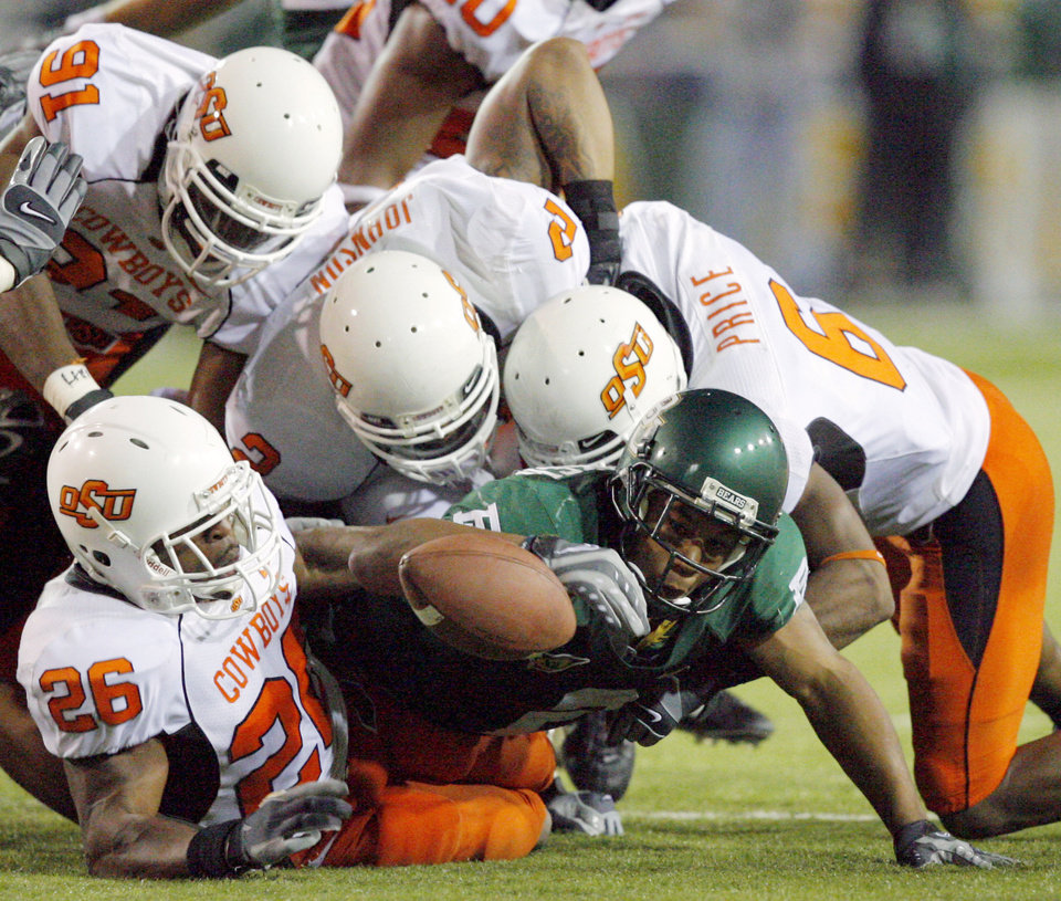Photo - OSU defensive players Quinton Moore (26) Ugo Chinasa (91) Rodrick Johnson (2) and Ricky Price (6) tackle and force a fumble on Baylor Brandon Whitaker in the second half during the college football game between Oklahoma State University and Baylor University at Floyd Casey Stadium in Waco, Texas, Saturday, Nov. 17, 2007. BY MATT STRASEN, THE OKLAHOMAN
