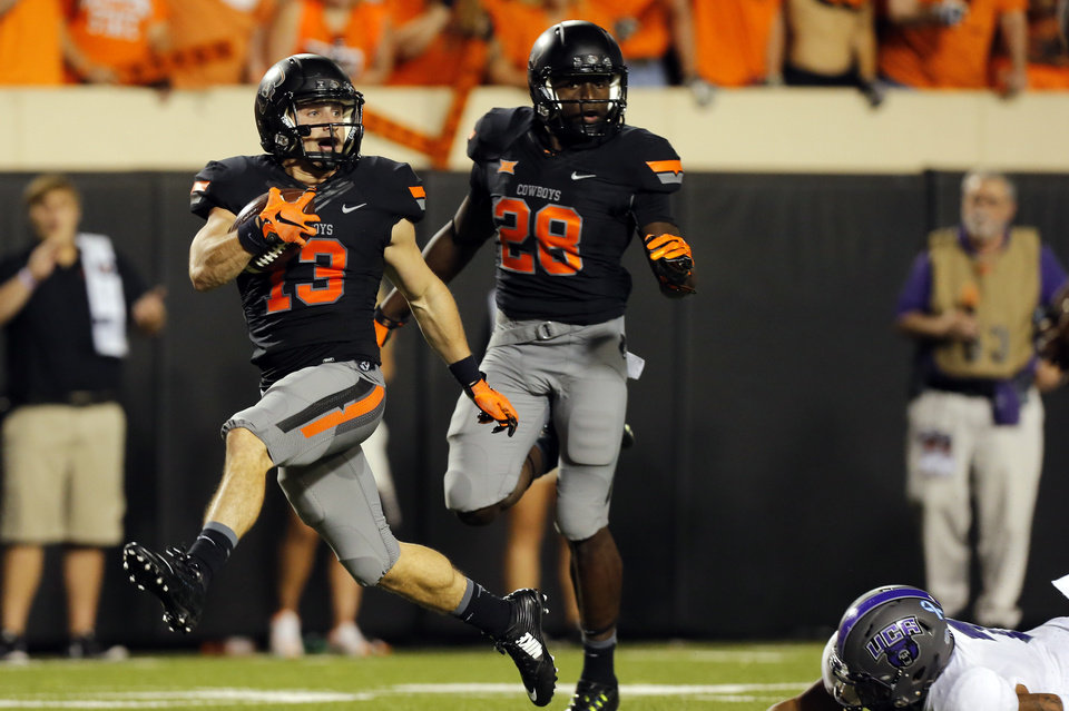 Photo - Oklahoma State's David Glidden (13) leaps as Central Arkansas' Bobby Watkins (7) tries to tackle him as he scores a touchdown in the third quarter  during the college football game between the Oklahoma State Cowboys (OSU) and the Central Arkansas Bears at Boone Pickens Stadium in Stillwater, Okla., Saturday, Sept. 12, 2015. Photo by Sarah Phipps, The Oklahoman