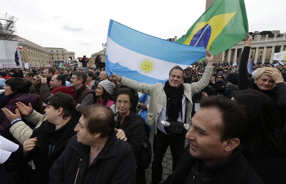 Photo - Visitors wave flags from Argentina and Brazil before the Angelus prayer by Pope Francis in  St. Peter's Square at the Vatican, Sunday, March 17, 2013. (AP Photo/Alessandra Tarantino)