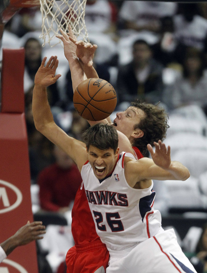 Atlanta Hawks shooting guard Kyle Korver (26) and Houston Rockets center Omer Asik battle for a rebound in the first half of an NBA basketball game on Friday, Nov. 2, 2012, in Atlanta. (AP Photo/John Bazemore)