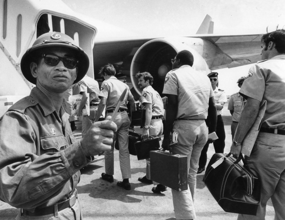 In this March 28, 1973 photo, a Viet Cong observer of the Four Party Joint Military Commission counts U.S. troops as they prepare to board jet aircraft at Saigonís Tan Son Nhut airport. As the last U.S. combat troops left Vietnam 40 years ago, angry protesters still awaited them at home. North Vietnamese soldiers took heart from their foes\' departure, and South Vietnamese who had helped the Americans feared for the future. While the fall of Saigon two years later — with its indelible images of frantic helicopter evacuations — is remembered as the final day of the Vietnam War, Friday marks an anniversary that holds greater meaning for many who fought, protested or otherwise lived it. (AP Photo/Neal Ulevich)