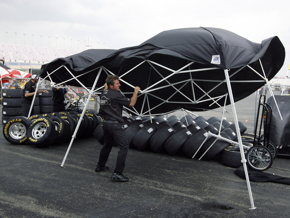 Photo -   Pete Michel, crew member for Jimmie Johnson, tries to hold down a tent as a storm blows through prior to the scheduled start of the NASCAR Nationwide Series auto race at Kentucky Speedway in Sparta, Ky., Friday, June 29, 2012. (AP Photo/James Crisp)