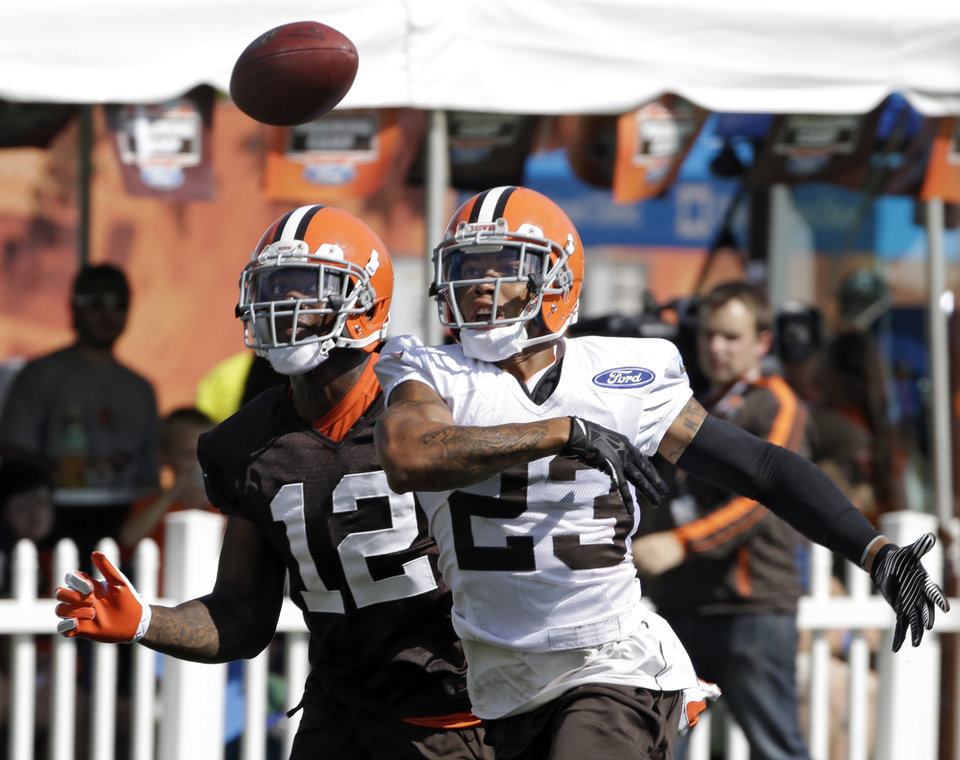 Photo - Cleveland Browns defensive back Joe Haden (23) defends a pass to wide receiver Josh Gordon (12) during NFL football training camp at the team's practice facility in Berea, Ohio Friday, July 26, 2013. (AP Photo/Mark Duncan)
