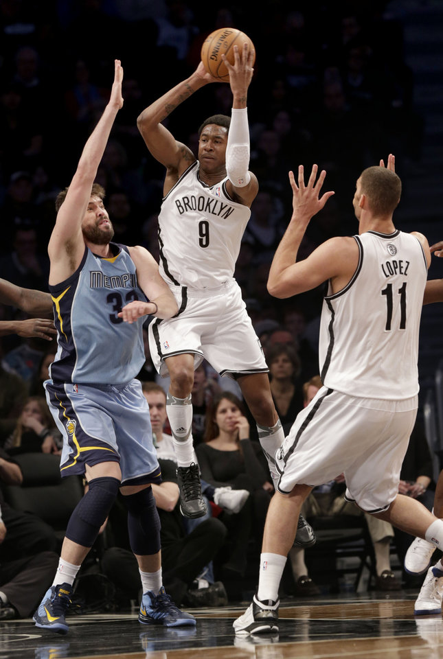 Brooklyn Nets' MarShon Brooks, center, looks to pass past Memphis Grizzlies' Marc Gasol, left, while Brook Lopez looks on during the first half of the NBA basketball game at the Barclays Center Sunday, Feb. 24, 2013 in New York.  (AP Photo/Seth Wenig)