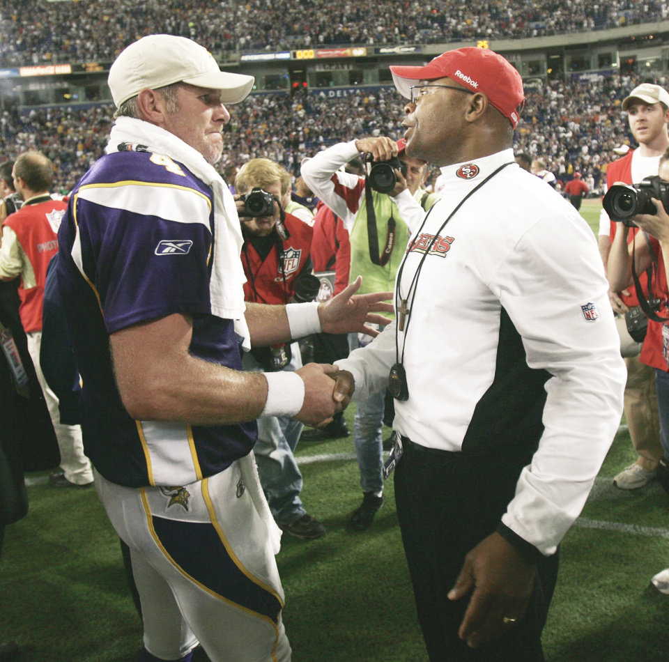 Photo - San Francisco head coach Mike Singletary, right, greets Minnesota quarterback Brett Favre on Sunday after the Vikings defeated the 49ers 27-24 on a last-second touchdown pass by Favre. AP photo
