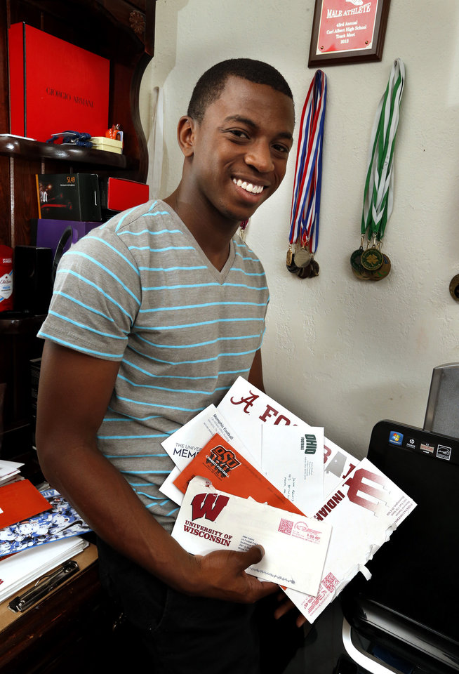 Photo - HIGH SCHOOL FOOTBALL PLAYER: Jalen Adams, Moore football player, shows some of his track medals and recruiting letters on Wednesday, June 19, 2013, in Moore, Okla.  Photo by Steve Sisney, The Oklahoman