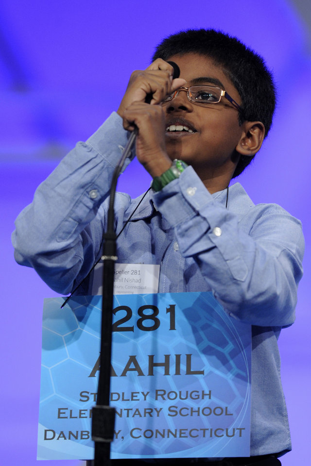 "Photo - Aahil Nishad, 9, of Danbury, Conn., struggles to get the microphone to his level before correctly spelling the word ""mahal"" during the 2015 Scripps National Spelling Bee in Oxon Hill, Md., Wednesday, May 27, 2015. (AP Photo/Cliff Owen)"