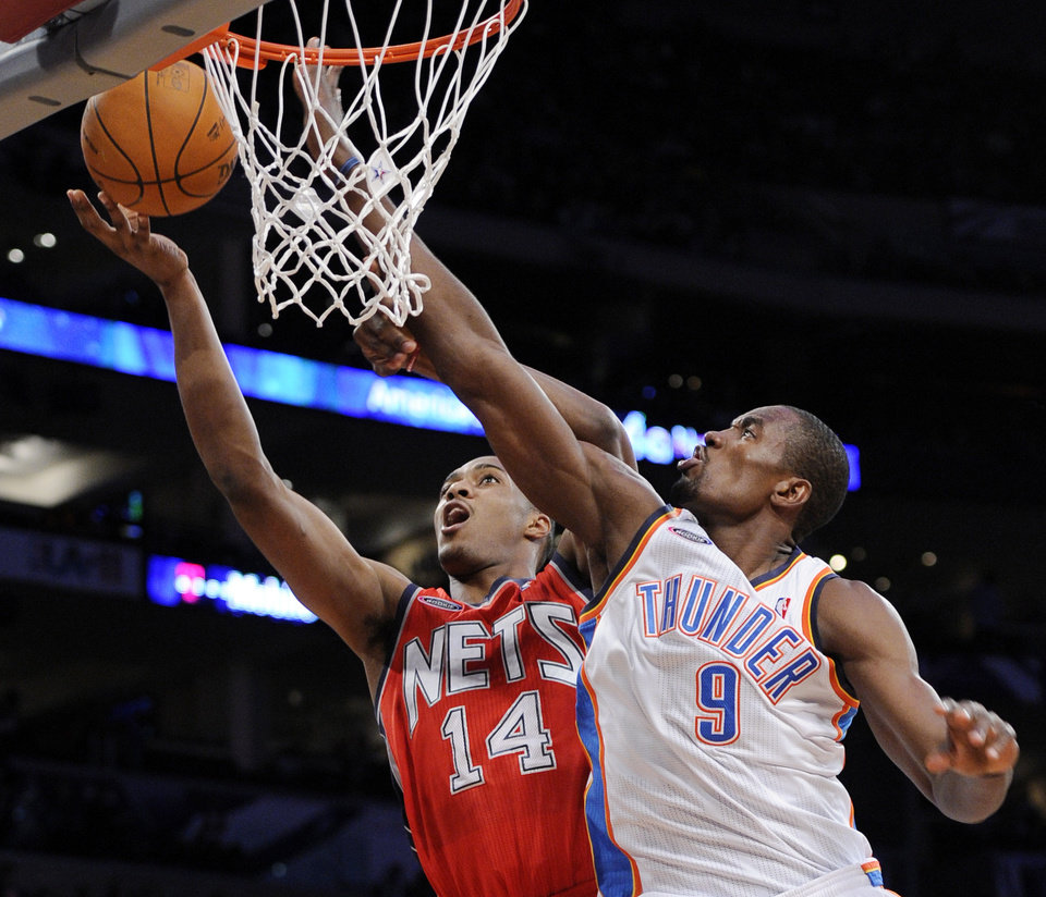 Photo - Sophomore Serge Ibaka, of the Oklahoma City Thunder, tries to block the shot of rookie Derrick Favors, of the New Jersey Nets, left, during the second half of the Rookie Challenge game during the NBA basketball All-Star Weekend, Friday, Feb. 18, 2011, in Los Angeles. (AP Photo/Mark J. Terrill)