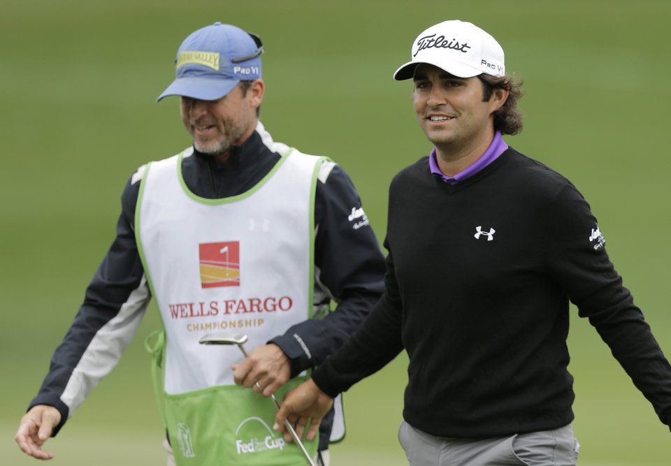 Photo - Martin Flores, right, smiles as he walks off the 18th green during the second round of the Wells Fargo Championship golf tournament in Charlotte, N.C., Friday, May 2, 2014. (AP Photo/Chuck Burton)