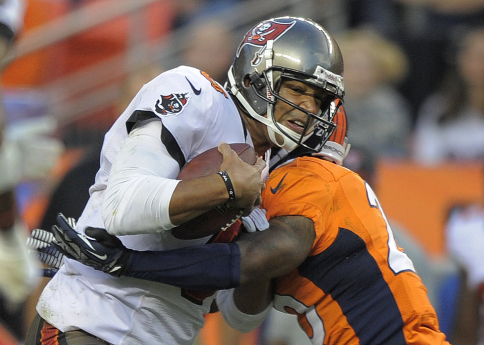 Photo - Tampa Bay Buccaneers quarterback Josh Freeman (5) is hit by Denver Broncos strong safety Mike Adams (20) in the third quarter of an NFL football game, Sunday, Dec. 2, 2012, in Denver. Denver won 31-23 and clinched the AFC West division. (AP Photo/Jack Dempsey)
