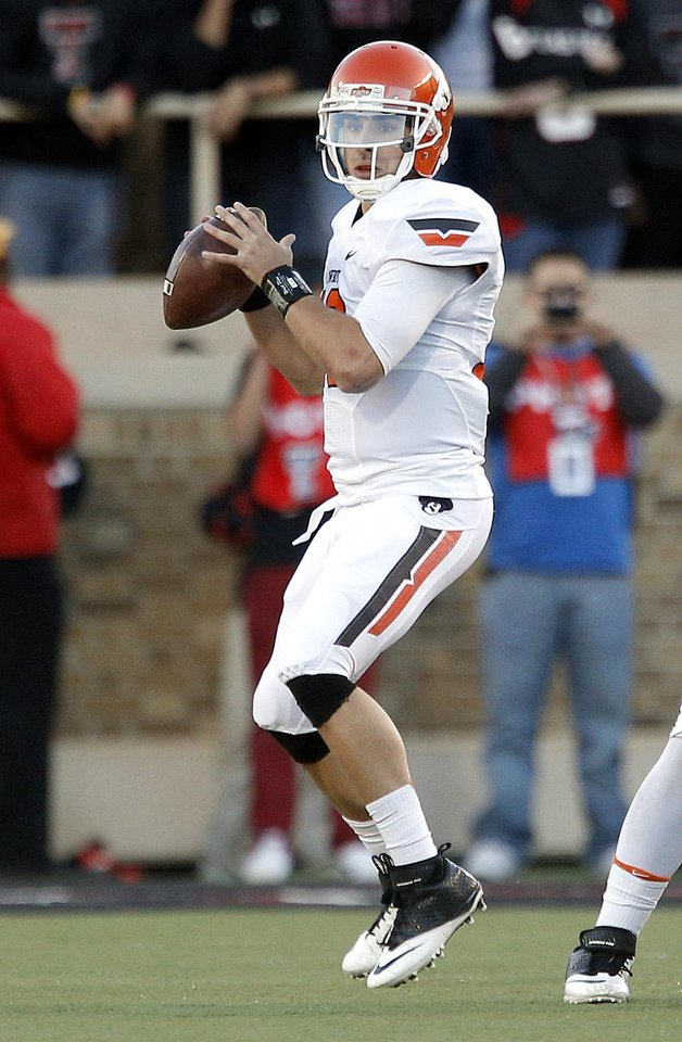 Oklahoma State 's Clint Chelf (10) looks to throw a pass during the college football game between the Oklahoma State Cowboys (OSU) and the Texas Tech Red Raiders (TTU) at Jones AT&T Stadium in Lubbock, Texas, Saturday, Nov. 2, 2013. Photo by Sarah Phipps, The Oklahoman