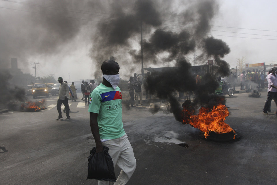 Photo - FILE- An Unidentified man stands near burning tyres during a protest on a major road junction in the commercial capital of Lagos, Nigeria, during a fuel subsidy protest in this file photo dated Tuesday, Jan. 3, 2012, as angry mobs call on the government to keep a cherished consumer subsidy that had kept gas affordable for more than two decades. A 30-minute film documentary called