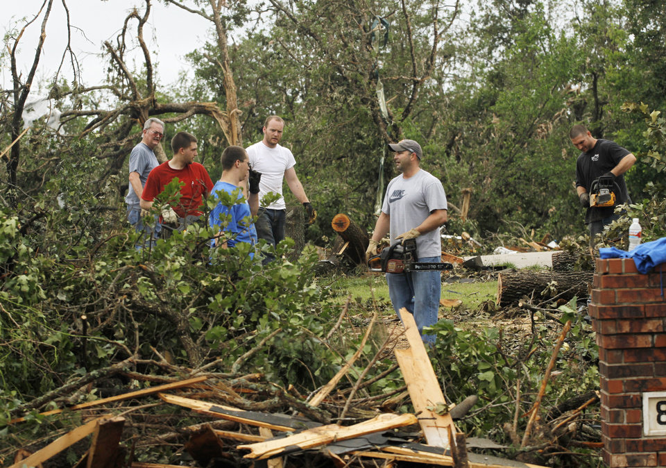 Dustin Moss, center, with chain saw, and others work to clear damaged trees in the Dripping Springs Estates Saturday, May 15, 2010. Saturday hundreds of volunteers went into areas that had been affected by last week's tornadoes to help clear debris. Photo by Doug Hoke, The Oklahoman.