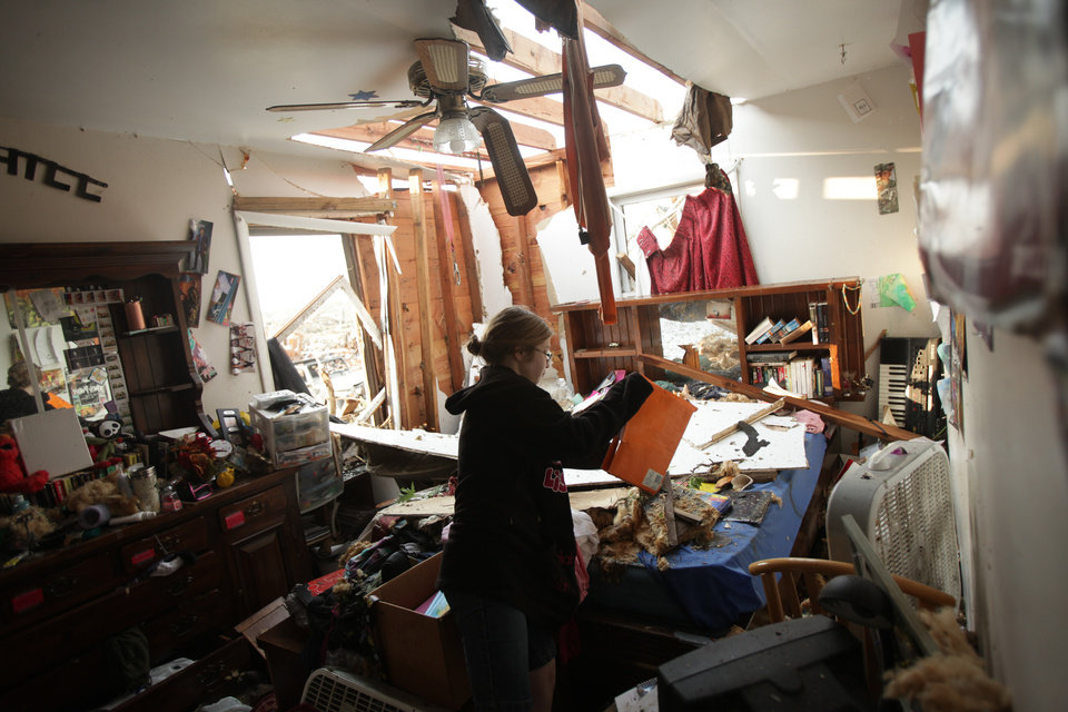 Photo - Candice Kell, 17, looks over her psychology textbook inside her grandmother's home in Joplin, Mo., Monday, May 23, 2011 after it was damaged by a tornado that destroyed nearly 30 percent of the town on Sunday afternoon. Kell and her grandmother, Jean Logan, rode out the storm in the laundry room. The twister cut a six-mile path through the city.  (AP Photo/Tulsa World, Adam Wisneski) ORG XMIT: OKTUL105